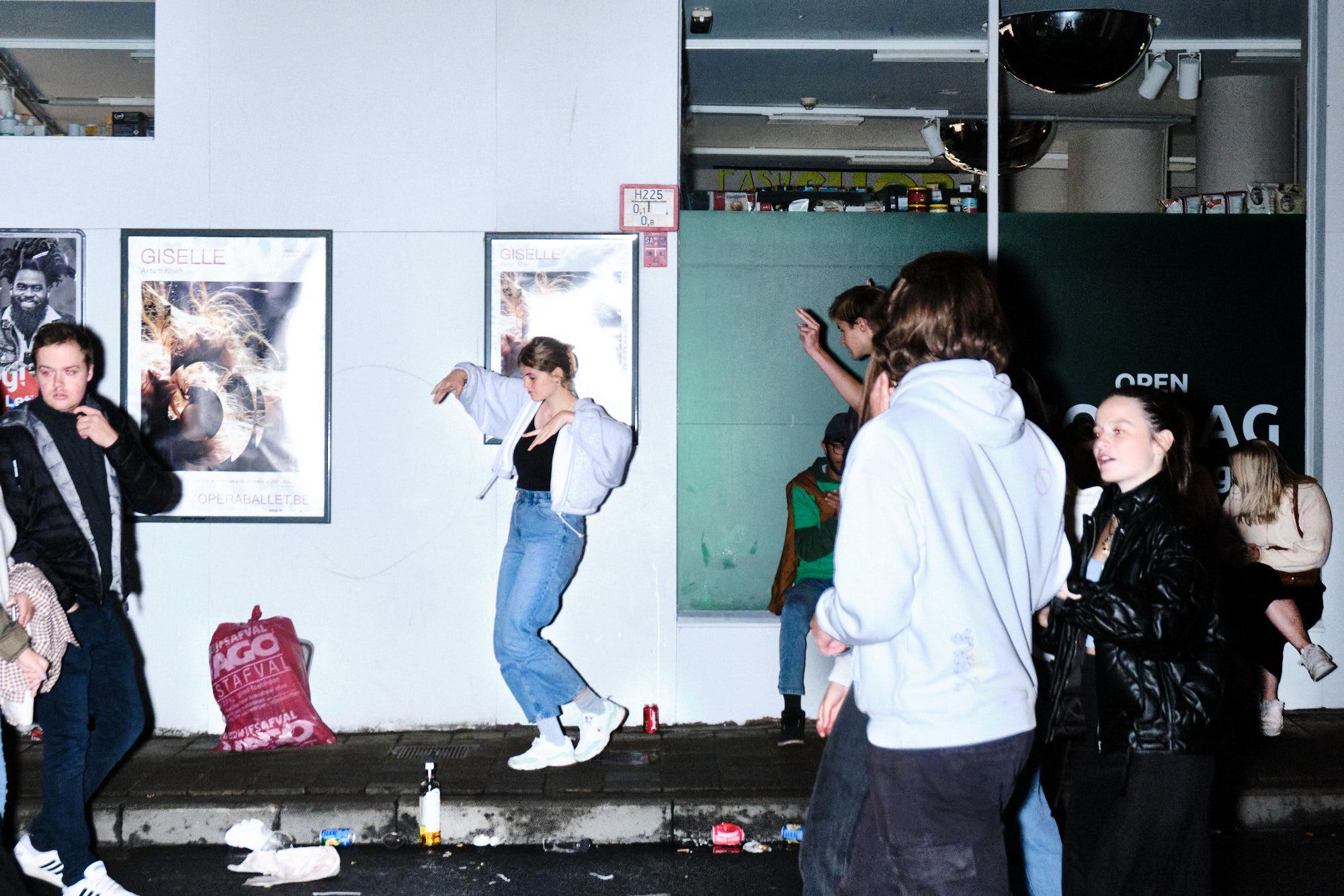 Een student danst in de overpoort rond afval